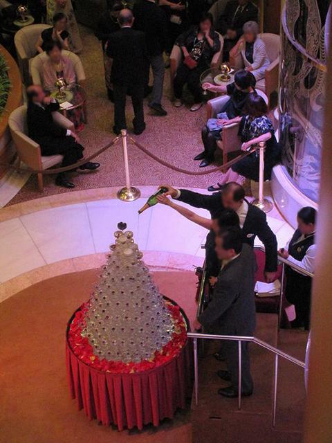 シャンパンタワーにシャンパンを注ぐカップル
